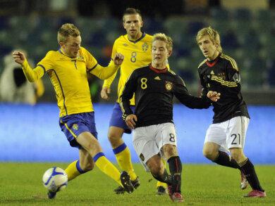 Debütant Lewis Holtby (m.) im Duell mit Schwedens Sebastian Larsson (l.)