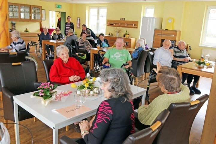 Die einzelnen Wohngruppen sitzen im großen Saal nach dem gemeinsamen Mittagessen zusammen.