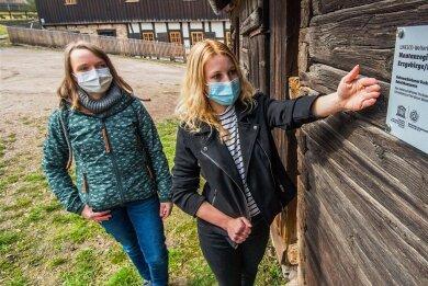 Wiebke Berkel (links) vom Welterbeverein und Laura Marie Espig, Koordinatorin Unesco-Welterbe bei der Stadt Schneeberg, zeigen eine Metallplakette an den Kobaltkammern des Siebenschlehener Pochwerks.