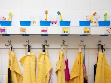 Handtücher und Zahnputzbecher hängen und stehen in einer Kindertagesstätte im Waschraum.