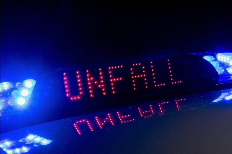 Das Blaulicht auf einem Fahrzeug der Polizei leuchtet in der Dunkelheit, während auf dem Display der Hinweis «Unfall» zu lesen ist. (Symbolbild)