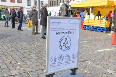 Auf dem Wochenmarkt auf dem Freiberger Obermarkt müssen Masken getragen und Abstände eingehalten werden. Schilder und farbige Linien sollen dabei helfen.