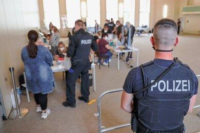 Bundespolizisten nehmen Fingerabdrücke von Verdächtigen: Zwei Zeitarbeitsfirmen sollen mit gefälschten Dokumenten vor allem Osteuropäer für Jobs in der Fleischindustrie nach Deutschland geholt haben.