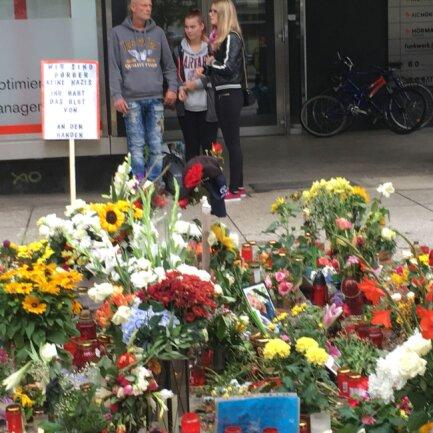 Eine kleine Gruppe steht mit einer Protestschild am Gedenkort für Daniel.
