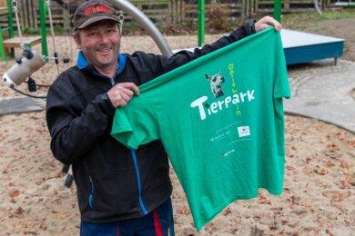Tierpark-Mitarbeiter Michael Bunke zeigt eines der T-Shirts, die der Tierpark Geithain verkauft, um Geld in die Kasse zu bekommen. Denn viele Veranstaltungen und der Weihnachtsmarkt mussten abgesagt werden.