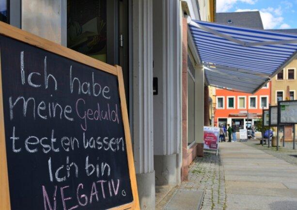 Mit Plakaten und Schildern zeigen viele Händler in Mittweida, was sie von den aktuellen Einschränkungen halten, hier der Buchladen am Markt.