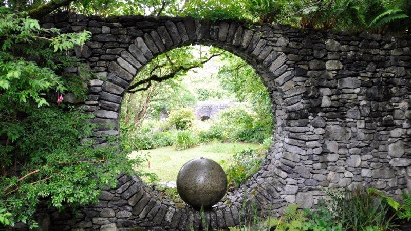 """Carl Wright - Rock 'n' Roll mal anders: Rocks, englisch für Steine, finden sich im """"Caher Bridge Garden"""" nicht nur im Untergrund. Carl Wright hat auch viele Mauern gebaut, mal wie hier als Sichtschutz und Hingucker zugleich, aber auch als kleine Stützen und Wegeinfassungen. Die runde Form der Bögen der alten Brücke, die dem Garten seinen Namen verlieh und hier im Hintergrund zu erkennen ist, waren ihm dabei besonders wichtig."""