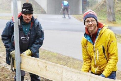 Nicht nur am Schreibtisch hat Patrick Burkhardt (r.) viel zu tun. Der Oberwiesenthaler Stützpunktkoordinator packt auch mit zu - so wie hier beim Umzäunen der Skiarena zusammen mit Hans-Peter Pötzsch.
