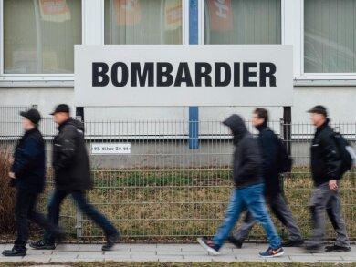 Mitarbeiter gehen am Werk von Bombardier vorbei.