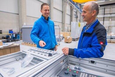 Marco Junghannß (l.), Mitarbeiter Einkauf und Zoll, und Mirko Hegewald, Mitarbeiter der Fertigungsleitung, besprechen sich zur Lieferung eines Bedienpultes.