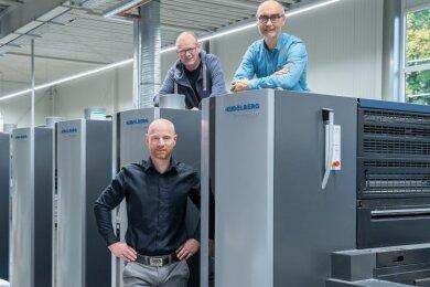 Lars Gröer (vorn), Hans Rother (oben links) und Dirk Hanus an der Druckmaschine.