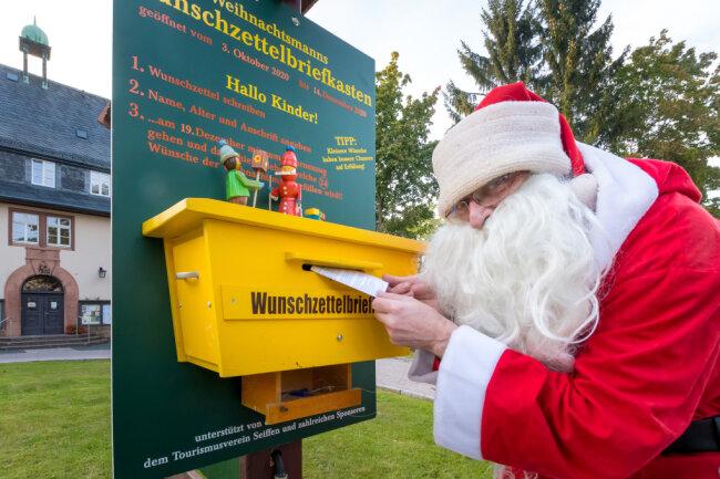 Der Weihnachtsmann, verkörpert von Axel Wiedemann, hat seinen Wunschzettelbriefkasten wieder vor dem Seiffner Rathaus angebracht.