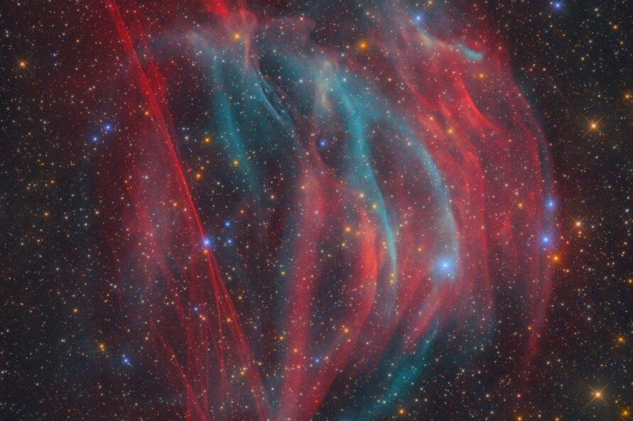 """Der Bärensteiner Nebel: Das Besondere an dem Foto sind die extrem filigranen und blutroten Filamente eines Supernova-Überrests, die im linken Bildbereich zu sehen sind. """"Ein Supernova-Überrest entsteht bei der Explosion von besonders großen und massereichen Sternen. Somit sind in diesem Foto gleich zwei gigantisch große Überreste ehemaliger Sterne zu sehen, was extrem selten ist"""", erläutert Marcel Drechsler."""