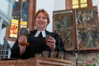 Die Erlauer Pfarrerin Astrit Zlotowski zeigt in der Erlauer Kirche extra angefertigte Keramik-Becher und einen Kelch.