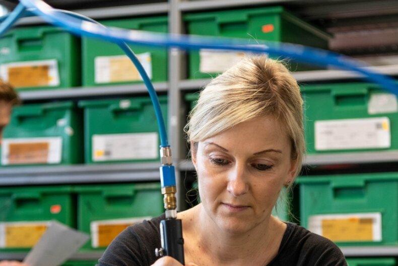 Jana Hentschel arbeitet in der Endmontage. Im Hintergrund Mitarbeiter Sven Seidel. Die einzelnen Produkte und Komponenten können im Hochhaus am Clemens-Pfau-Platz dank des Lastenaufzugs und mit Paletten gut hin- und hergefahren werden.