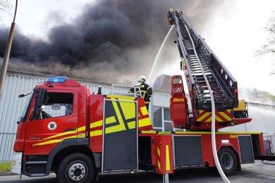 Von Drehleiter und Hubwagen aus versuchten die Feuerwehrleute, den Brand im Dachbereich der Werkhalle bei Ertex zu löschen.