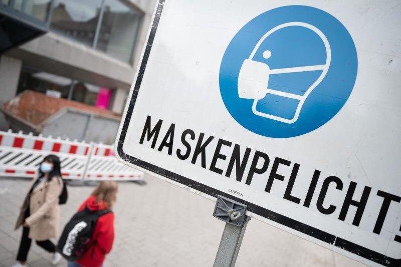 Zwei Passantinnen gehen in einer Fußgängerzone hinter einem Schild vorbei, auf dem «Maskenpflicht» steht.