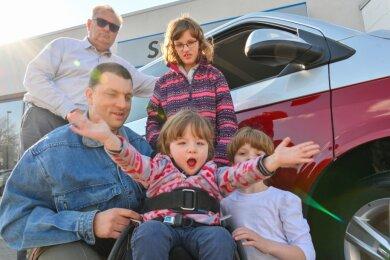 Michael Gawlitta (hinten links), Mitarbeiter des des Autohauses Schneider, hat das neue Familienauto übergeben. Nico Günthel und seine Töchter Mia (Mitte), Lea (dahinter) und Michelle freuen sich sehr über das rot-weiße Gefährt.