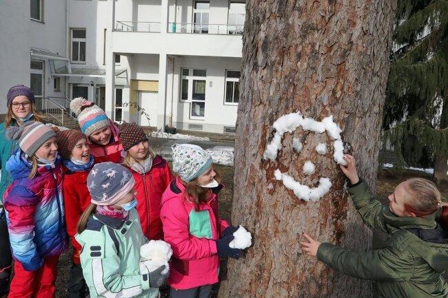 """An der Evangelischen Grundschule """"St. Martin"""" in Meerane nutzen diese Schülerinnen der vierten Klasse Schneereste für freundliche Schneegesichter an den Bäumen des Schulhofes."""