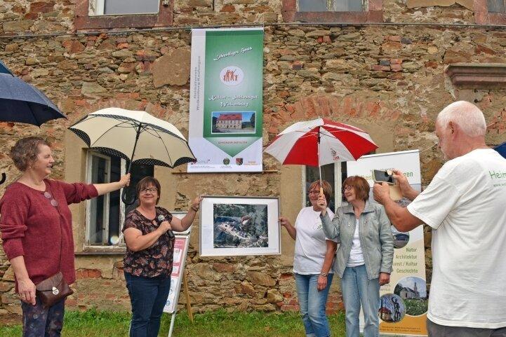 Das frühere Herrenhaus des Schlossgutes Wolkenburg soll erhalten bleiben. Zur Eröffnung einer Ausstellung am Sonnabend bei Regen übergibt Ortsvorsteherin Annett Groh (2. von links) der Vereinschefin Katrin Kaminsky (2. von rechts) eine Luftaufnahme vom Schlosskomplex.