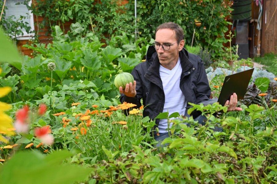 Thomas Seidel in dem Garten, in dem er Gemüse - unter anderem diese Zucchini-Art - anbaut, das er auch im Internet zum Tausch anbietet.