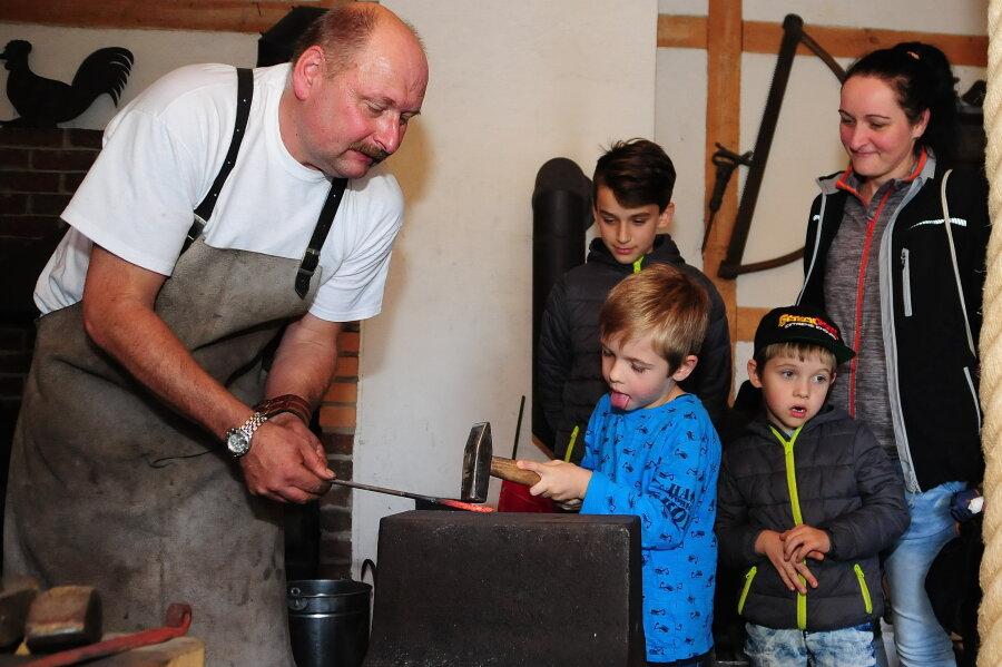 Hobbyschmied Jens Langer hatte neugierige Gäste: Susan Rösner aus Marienberg zählte mit ihren Jungs Ryan, Logan und Marlon (v. r.) zu den knapp 500 Besuchern in Lauta.