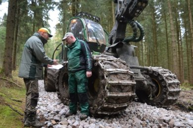 Dort, wo die Erntemaschinen aus dem Wald fahren, wurde Schotter aufgetragen, in dem der Schlamm hängen bleiben soll. Im Bild Förster Dirk Schönfelder (links) im Gespräch mit Harvesterfahrer Jens Zehrmann.