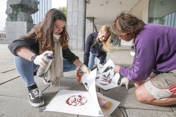 Giuliana Bollmann und Louisa Braune vom Andrégymnasium probieren mit Michael Drostek von der Rebel-Art-Galerie Schablonengraffiti.