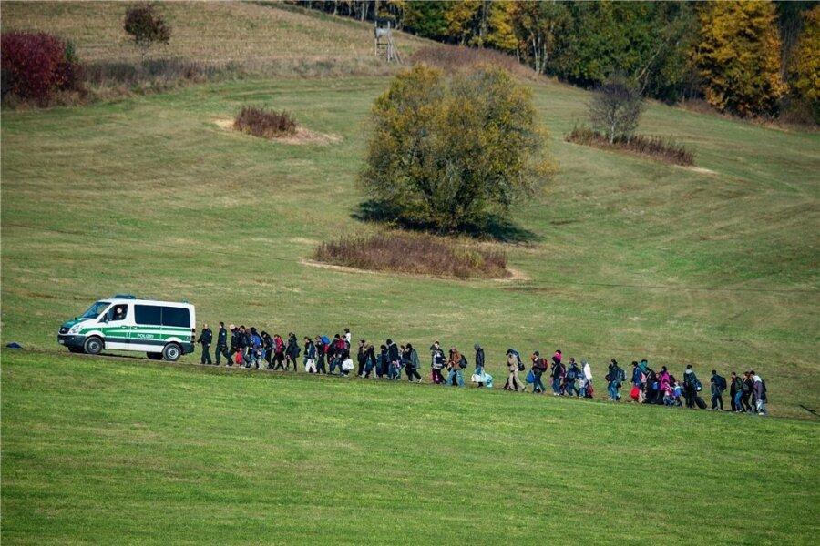 Die Polizei geleitet einen Gruppe Flüchtlinge zu ihren provisorischen Unterkünften.