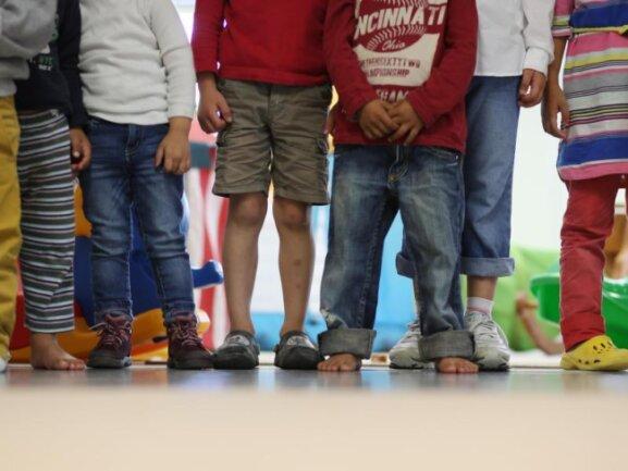 Kinder stehen in einem Kindergarten.