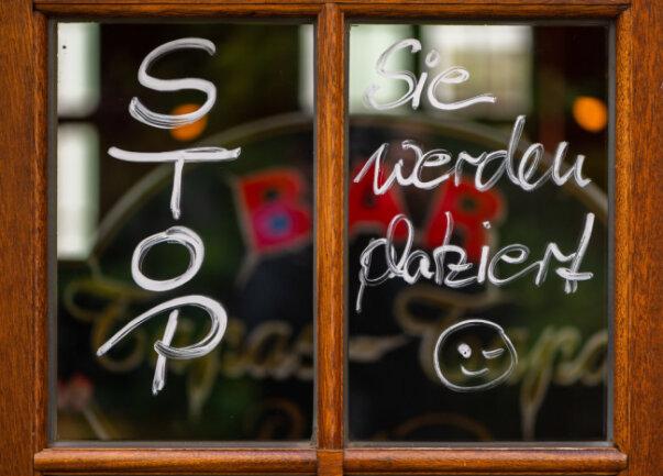 """An der Eingangstür eines spanischen Restaurants in Dresden steht: """"Stop. Sie werden platziert"""". Sachsen will die meisten der bereits angekündigten Corona-Lockerungen auf diesen Freitag vorziehen. Unter strengen Hygieneauflagen darf die Gastronomie ab dem 15. Mai 2020 wieder öffnen."""