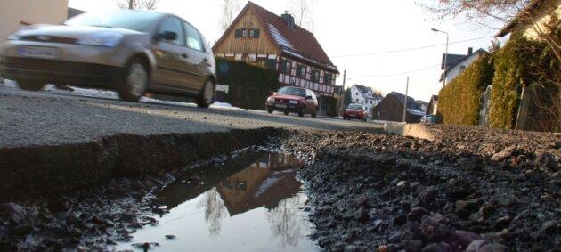Kraterlandschaft in Rödlitz. Auf der Hauptstraße sind die Schlaglöcher teils so tief, dass sich in ihnen Pfützen bilden.