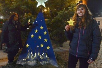 """Sindy Kosch vom Jugendstadtbüro (links) und Carolin Schmidt von der Touristinfo koordinieren die Adventsaktion """"Sterne über Auerbach"""". Zu finden sind die Wünsche an der Pyramide auf dem Neumarkt."""