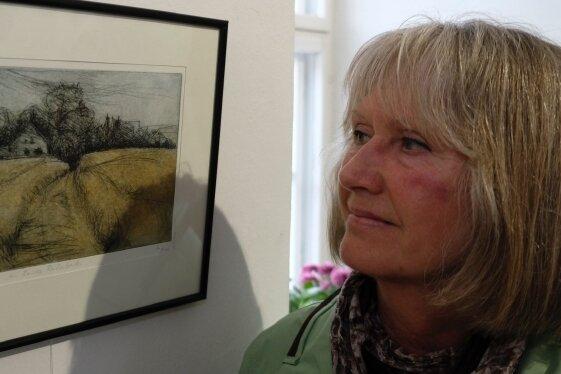 """Hannelore Weiß betrachtet die ausgestellte Kaltnadelradierung """"Am Rande Reichenbachs"""" ihres 2014 verstorbenen Mannes."""