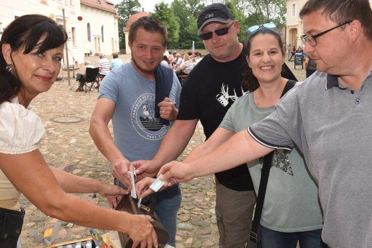 Astrid Grübner (links) behielt bei der Aktion von Ritter Harras alias Rolf Pönicke in Lichtenwalde die Spendenbox im Blick. Zahlreiche Zuschauer gaben Geld, auch Mike Endtmann (rechts) aus Lichtenwalde.