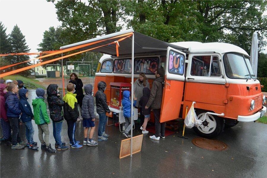 Der Inselkino-Kinobus macht Station dem Hof der Grundschule Dorfstadt. Für das Kinoerlebnis im rollenden Filmtheater gibt's am Eingang zwar keine Eintrittskarte, aber dafür eine Tüte Popcorn.