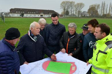 Nach dem ersten Spatenstich haben sich am Donnerstag die Vertreter der Verwaltung und Sportler den Bauplan für das neue Sportforum an der Pflaumenallee in Hainichen angeschaut.