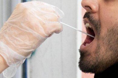 Ein Patient lässt vor einer Arztpraxis einen Abstrich machen.