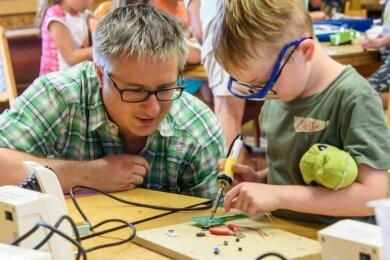 Mit Unterstützung von Hochschulmitarbeiter Falko Jahn lötet Eddie unterm Dach des Müllerhofs einen Morsetaster zusammen. Am ersten Technikcamp in Mittweida nehmen 21 Kinder teil.