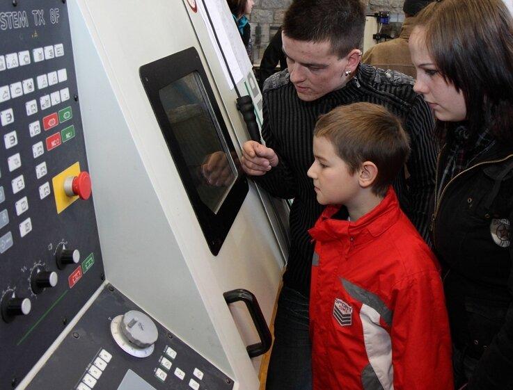 """<p class=""""artikelinhalt"""">Der angehende Zerspanungsmechaniker Anton Weigel erklärt Josua Meyer und seiner Schwester Eva die Funktionsweise einer CNC-gesteuerten Drehmaschine.</p>"""
