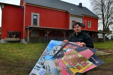 """Clubchef Max Kermes zeigt alte Plakaten zu """"Krach am Bach"""" vor dem Jugendclub Berthelsdorf in Hainichen. Auf dieser Wiese haben in vorigen Jahren am Pfingstsonntag etwa 3000 Gäste gefeiert."""