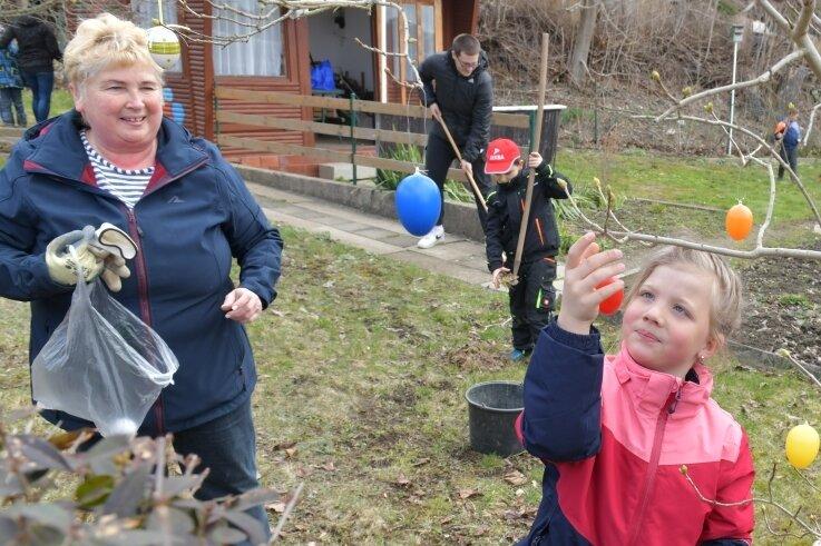 """Sozialpädagogin Heike Lorenz ist zum Frühjahrsputz mit Kindern im """"Grünen Klassenzimmer"""", einem Garten in der Anlage """"Brüllender Löwe"""". Leonie (6) schmückt derweil einen Osterbaum."""