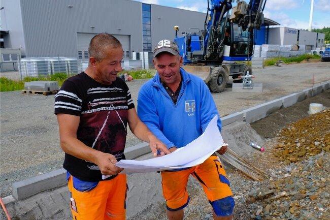 Hoch- und Tiefbau Reichenbach bereitet derzeit den Bau der neuen Halle vor, dazu gehört auch der Bau einer neuen Ausfahrt zum Werkstor. Polier Rico Kaiser (rechts) im Gespräch mit Mitarbeiter Thomas Martin.