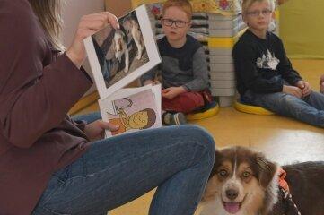 Anhand von Bildern klärt die Kita-Leiterin über Verhaltensweisen der Hunde auf.