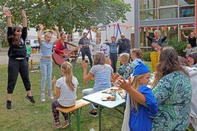 Die Vorfreude auf den neuen Spielplatz ist groß. Doreen Schöps an der Gitarre begleitet den Gesang der Kinder auf dem Platz vorm Gemeindezentrum der Versöhnungskirchgemeinde in Planitz.