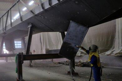 Am Mittwoch wurde für den Antransport dieses Brückenteils an die Eschenstraße noch die B 94 gesperrt, jetzt laufen die für die Beschichtung der Baustahl-Konstruktion nötigen Arbeiten - Andreas Berthum beim Sandstrahlen des 30 Meter langen Teils.