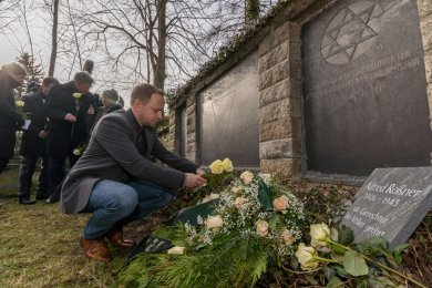 Zum 75. Jahrestages der Befreiung des KZ Auschwitz fand am 27. Januar 2020 auf dem Falkensteiner Friedhof am bisherigen Gedenkstein von Alfred Roßner eine Gedenkfeier mit prominenter Teilnahme statt. Der stellvertretende Bürgermeister und CDU-Stadtrat Ronny Kadelke (vorn im Bild) versprach damals, dass die Grundschule nach Roßner benannt werde. Ein Dreivierteljahr später war davon keine Rede mehr. Man sei der Meinung, dass eine Stele mit Tafel plus ein jährlicher Preis mehr Andenken garantiere als die Benennung eines Gebäudes nach Roßner, so Kadelke heute.