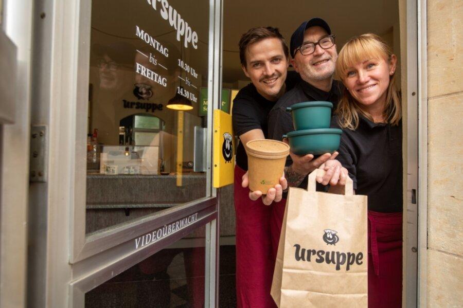 """Mit Inkrafttreten der 3G-Regel stellt die """"Ursuppe"""" den Restaurantbetrieb wieder ein. Das Essen kann nachhaltig verpackt bei Christopher Eichler, Mick McSorley und Larisa Oberhauser (von links) abgeholt werden"""