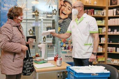 Auch Gabriele Langnickel hat am Dienstagfrüh ihre Gratis-Masken in der Zwickauer Apotheke am Meistereck entgegengenommen. Dabei hilft auch Chef Jan Bittersohl mit, der sich für die Vorbereitungen deutlich mehr Vorlauf gewünscht hätte.