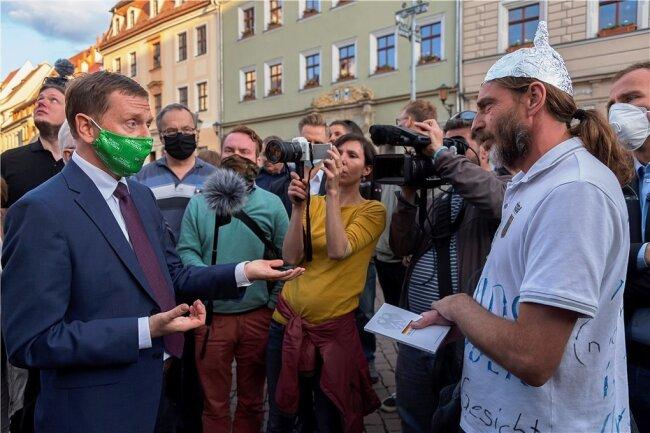 Ohne Überzeugung: Sachsens Ministerpräsident Michael Kretschmer (links) im Gespräch mit einem Gegner der Corona-Maßnahmen. Debatten können allerdings nur dann funktionieren, wenn sie ein verbindendes Element als gemeinsame Basis aufweisen.